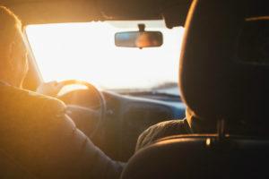 Mann som kjører bil med sol som blender inn gjennom frontruten