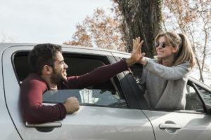 En mann og en kvinne som gir hverandre high five gjennom hver sitt bilvindu