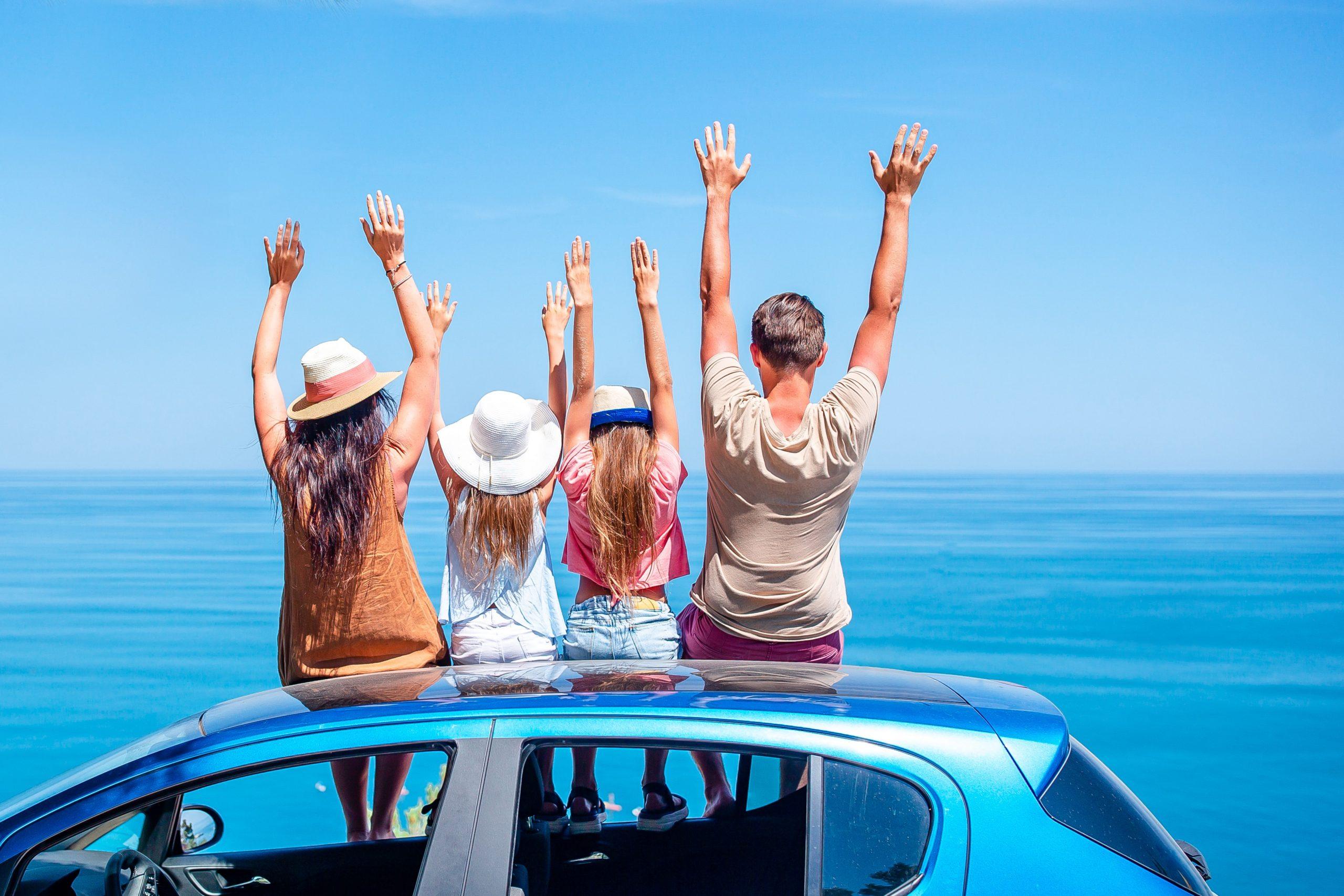 Bilde av en familie på ferie som sitter oppå bilen