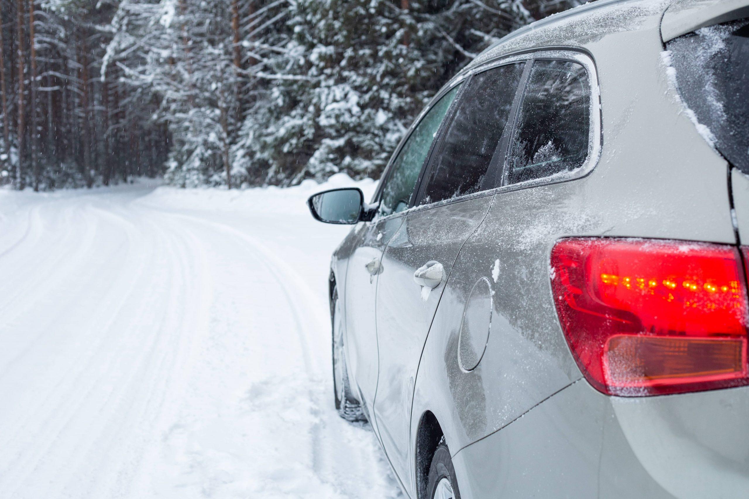 Bilde av en suv bil i vinterlandskap på veien med skog i bakgrunnen