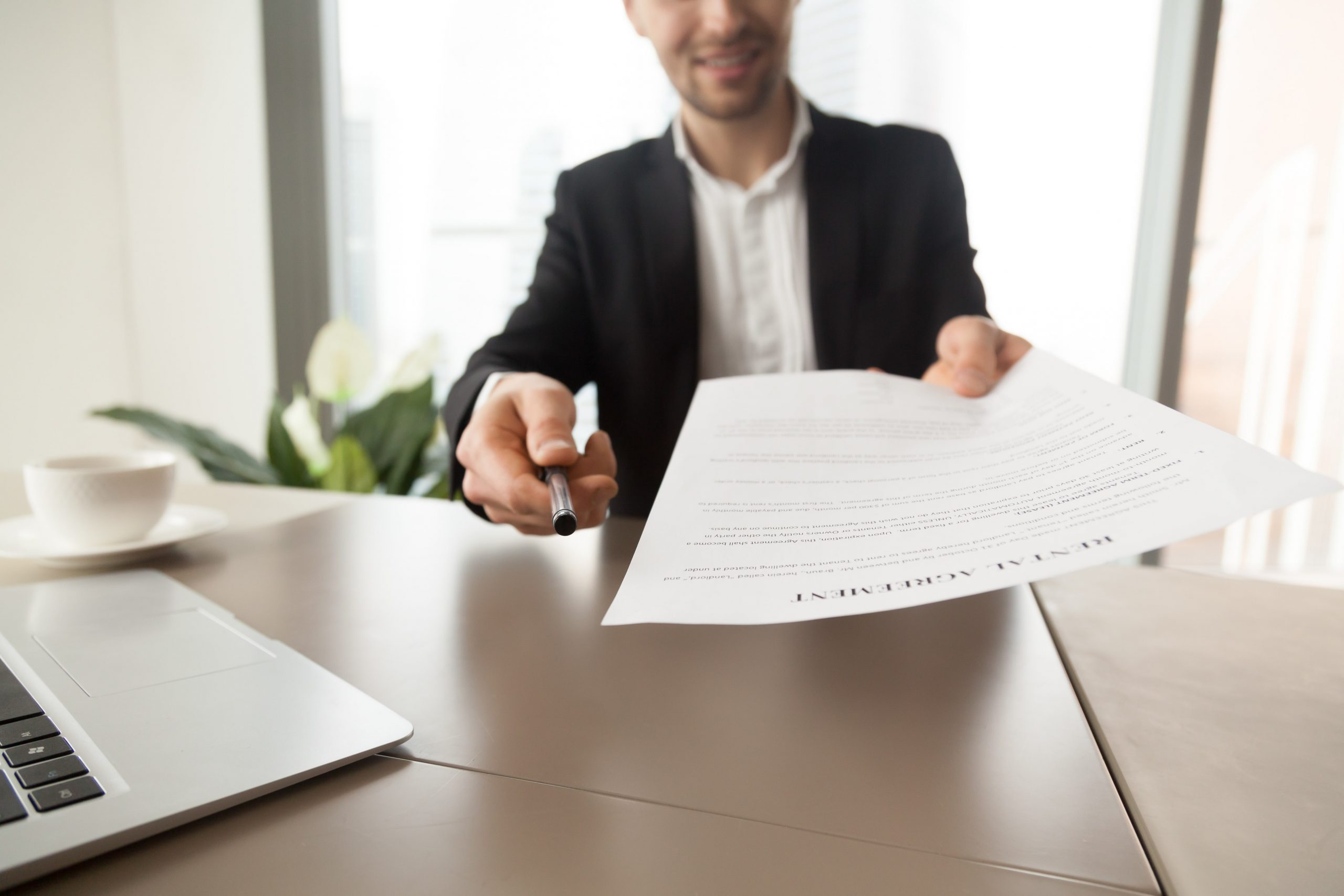 bilde av en mann som gir deg en kontrakt med vilkår og betingelser