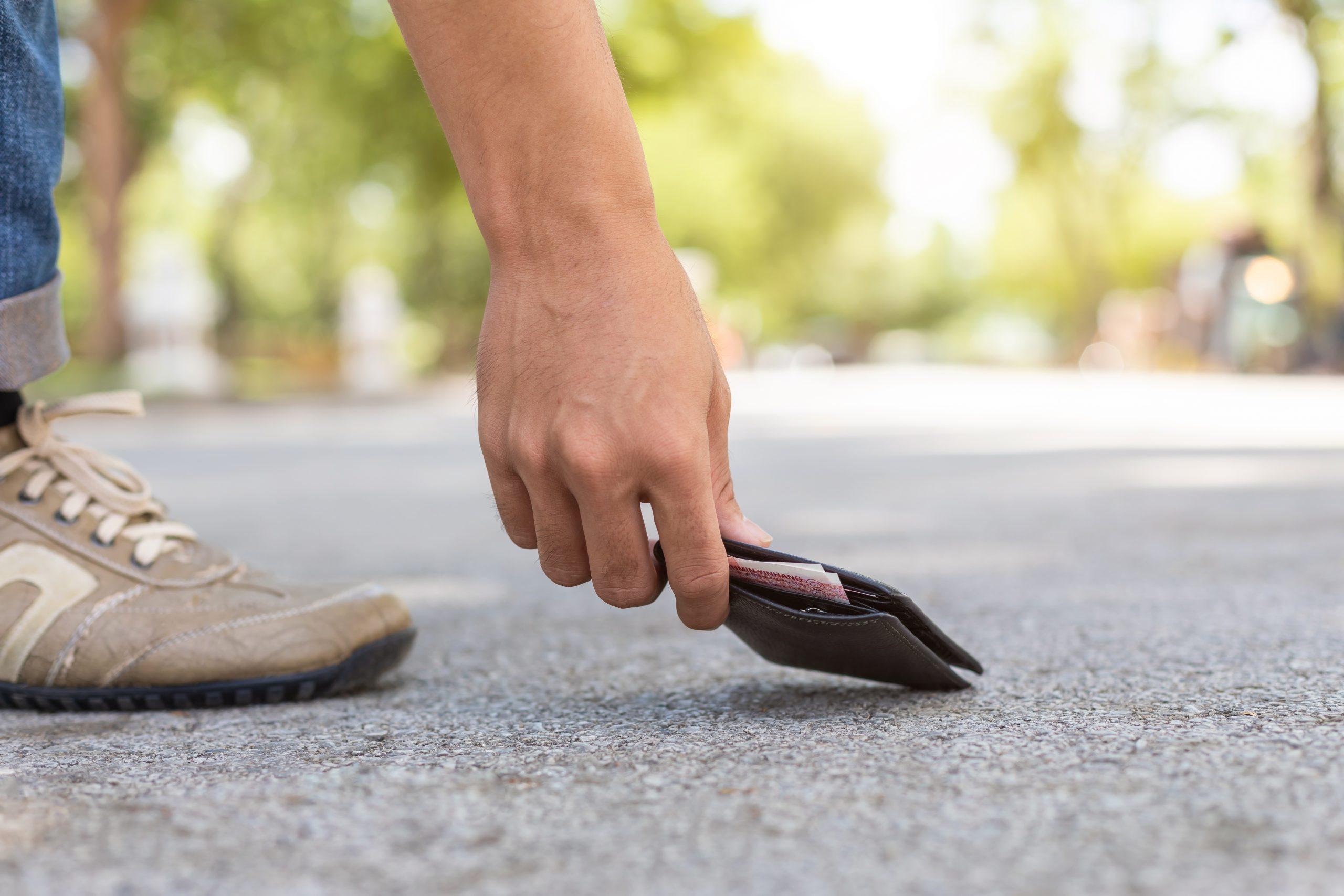 En mann som plukker opp en lommebok som er mistet på veien.